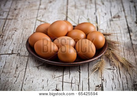fresh brown eggs in plate and wheat ears on rustic wooden background