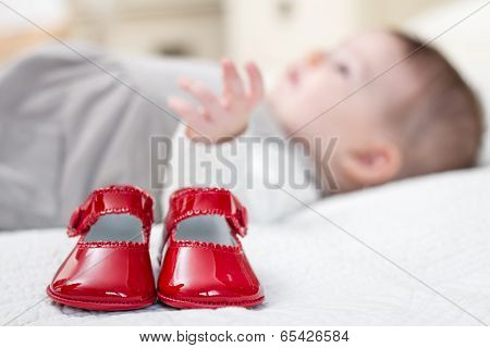 Baby red shoes and babe lying on the background