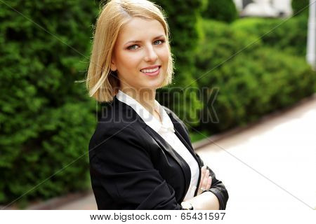 Portrait of a happy beautiful woman with arms folded in park