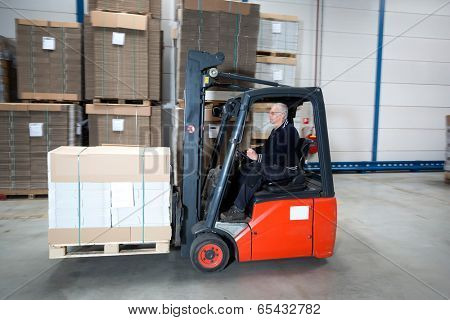 Forklift driving through a nice and clean warehouse. The experienced driver is transporting a pallet full of cardboard boxes.