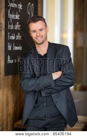 Portrait of smart young businessman standing arms crossed in coffeeshop