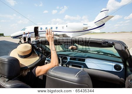 Woman in convertible waving hand to pilot and stewardess against private jet at airport terminal
