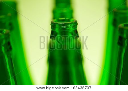 Ten Green Bottles In Three Rows Shot With Green Light. Central Bottle Neck In Focus.
