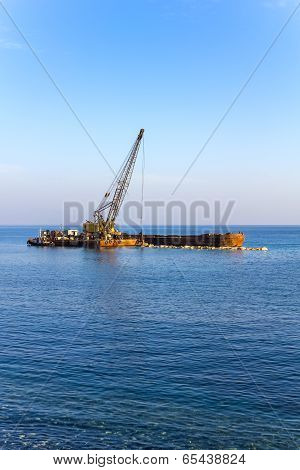 The Elevating Crane Unloads Stones From The Barge At Sea.