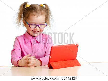 smiling kid in glasses looking at mini tablet pc screen sitting at table