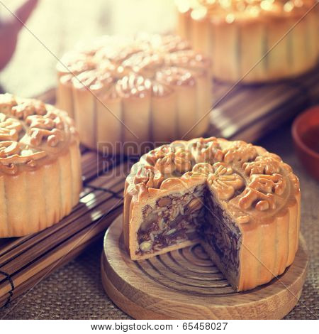 Retro vintage style Chinese mid autumn festival foods. Traditional mooncakes on table setting with teacup. The Chinese words on the mooncakes means assorted fruits nuts, not a logo or trademark.