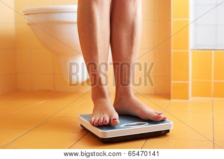 A Pair Of Female Feet On A Bathroom Scale