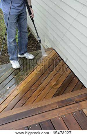 Man Spray Cleaning Deck