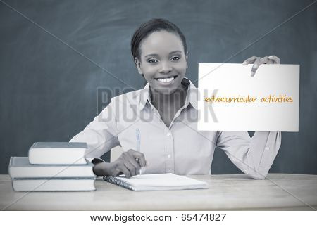 Happy teacher holding page showing extracurricular activities in her classroom at school