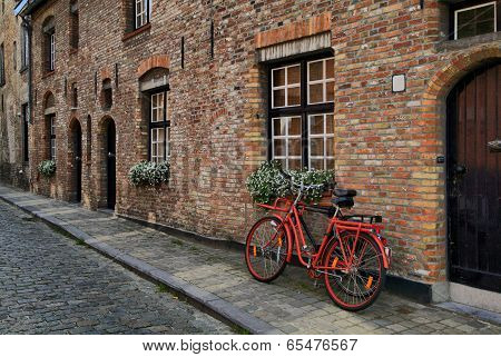 Red Bicycle Near The Window Of Brick House In Brugge