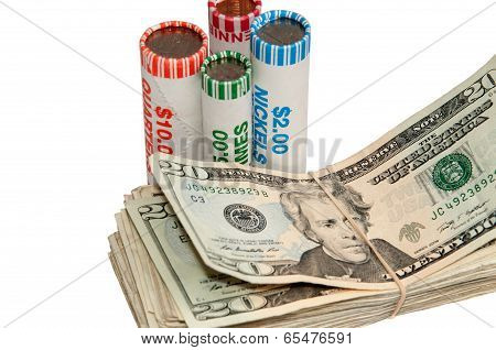 Stack Of Usa Currency And Rolls Of Coins