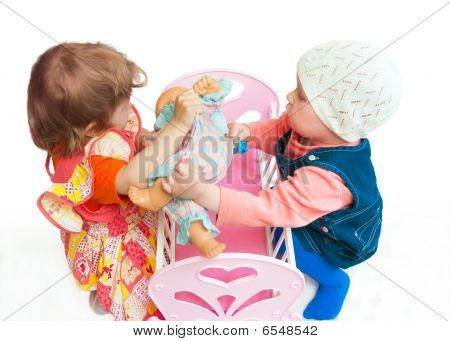 Two Little Girls Divide A Doll