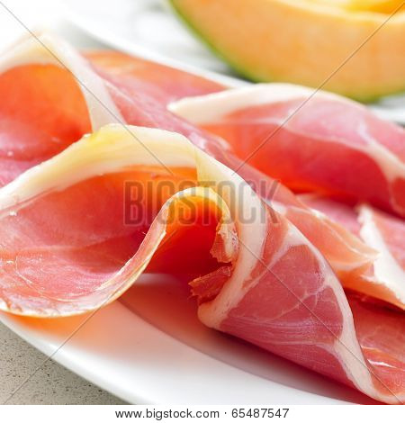 closeup of a plate with spanish jamon serrano and some slices of melon in the background, to prepare melon con jamon, a typical summer dish in Spain