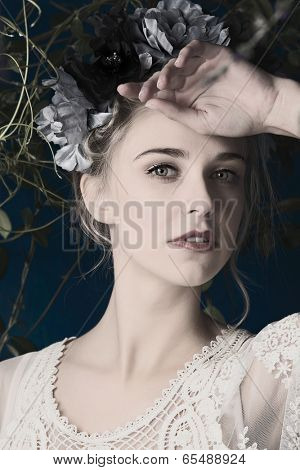 Portrait of a beautiful woman with natural makeup. Wearing silk flower headpiece on grunge plant background