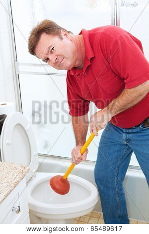 Man using a plunger to unclog a bathroom toilet.