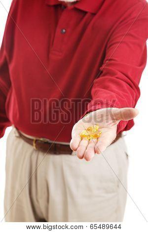 Closeup of senior man's hand holding omega-3 fish oil capsules.