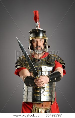 Portrait of Roman centurion holding sword over a neutral background