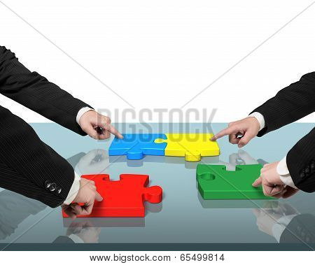 Four People Assembling Puzzles On Table