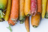 stock photo of end rainbow  - stacked bunch of organic rainbow carrots for sale at the local farmers market - JPG