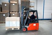 stock photo of forklift driver  - Forklift driving through a nice and clean warehouse - JPG