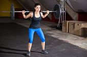 foto of squatting  - Beautiful Hispanic woman doing some squats with a barbell in a cross - JPG