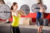 stock photo of squatting  - Cute brunette and a guy doing some squats with barbells in a  gym - JPG