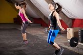 picture of jump rope  - Pretty athletic girls using jump ropes for her workout in a gym - JPG