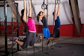 foto of pulling  - Group of three people pulling their weight up in the gymnastic rings in a crossfit gym - JPG