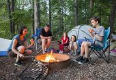 stock photo of tent  - family of five people camping and having fun cooking over fire - JPG