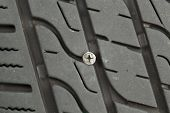 picture of unsafe  - Closeup horizontal photo of wood screw embedded into car tire tread - JPG