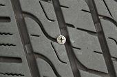 stock photo of unsafe  - Closeup horizontal photo of wood screw embedded into car tire tread - JPG