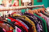 stock photo of flea  - Clotes hanging on a rail at a street market outdoors - JPG