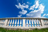 foto of balustrade  - Old white stone balustrade on green grass with blue sky and clouds in the background - JPG