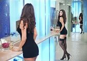 pic of black heel  - Sensual woman wearing a black short dress posing in a modern scenery - JPG