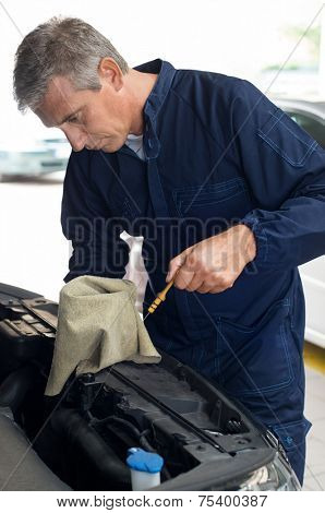 Mature Mechanic Measuring The Oil Level Of A Car Engine In Garage