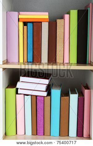 Books on wooden shelves close-up