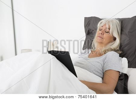 Woman with closed eyes and a book in bed