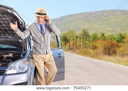 Senior having a problem with his car on an open road