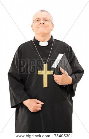 Mature priest holding a bible and looking up isolated on white background