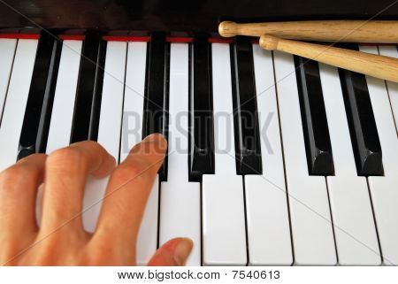 Left Hand Playing On Piano Keyboard With Drum Sticks