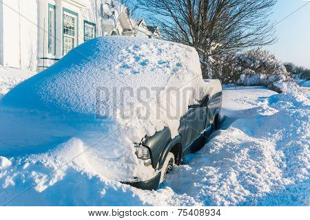 A quart ton truck buried under snow in a suburban driveway.