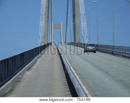 Car driving over a big bridge