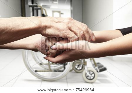 Hands of an elderly man holding the hand of a younger woman on wheelchair background