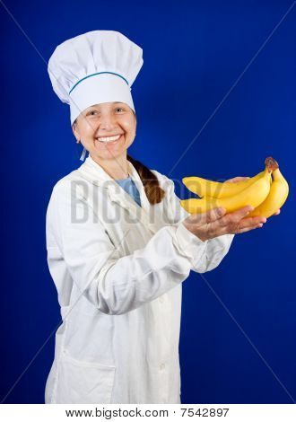 Female Cook Holding Yellow Hand Of Bananas