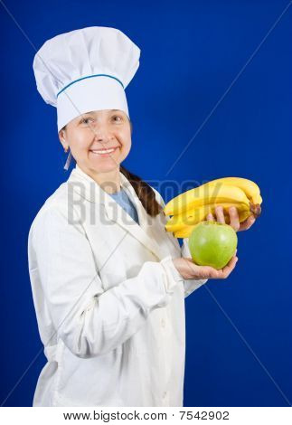 Cook Holding Hand Of Bananas And Apple