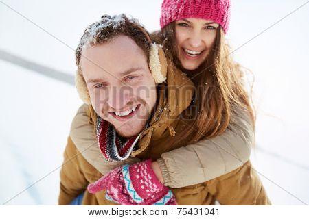 Portrait of happy young couple in winterwear having fun outside