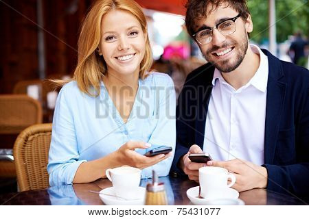 Cheerful man and woman with cellphones looking at camera in cafe