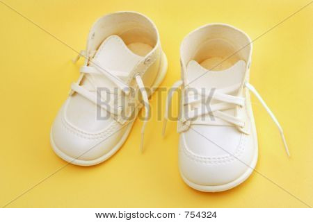 baby shoes over yellow