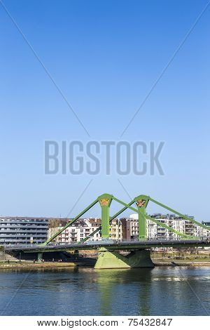 FRANKFURT GERMANY - MARCH 3 2014: View of the city with Floessserbruecke with river Main in Frankfurt Germany. The Floesser bridge was inaugurated in 1984 and has a length of 221 meter.