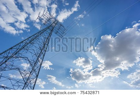 Wide view of electric tower over blue sky and clouds